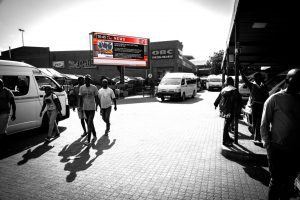 Commuters at a taxi rank viewing large format digital screen